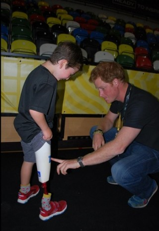 Prince Harry Looks At Rio Woolf's Prosthetic Leg