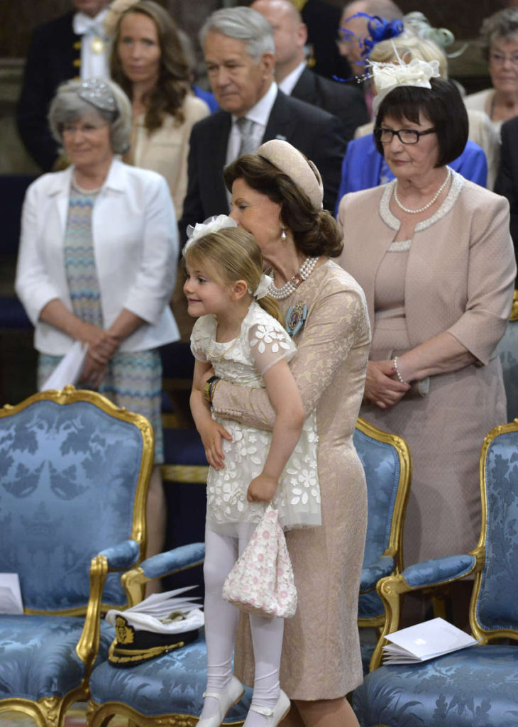 queen silvia pink outfit holds up princess estelle prince oscar christening