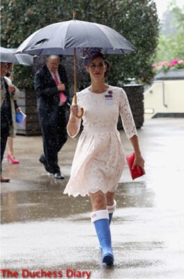 woman holds umbrella cream lace dress blue wellies royal ascot day one