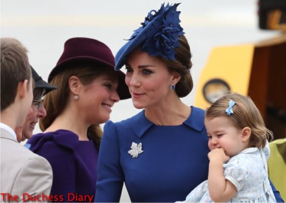 kate middleton chats others holds princess charlotte victoria airport